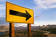 Yellow road sign with large black arrow on a curving dirt road in Flaming Gorge, Wyoming, USA.