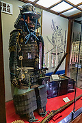 "Samurai armor exhibit. Matsumoto Castle is a ""hirajiro"" - a castle built on plains rather than on a hill or mountain, in Matsumoto, Nagano Prefecture, Japan. Matsumotojo's main castle keep and its smaller, second donjon were built from 1592 to 1614, well-fortified as peace was not yet fully achieved at the time. In 1635, when military threats had ceased, a third, barely defended turret and another for moon viewing were added to the castle. Interesting features of the castle include steep wooden stairs, openings to drop stones onto invaders, openings for archers, as well as an observation deck at the top, sixth floor of the main keep with views over the Matsumoto city."