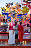 Europe, Germany, North Rhine-Westphalia, Ruhr area, Herne, the kermis in the district Crange [the kermis in Crange is the biggest fair in North Rhine-Westphalia], Turkish woman with her children in front of a carrousel.....Europa, Deutschland, Nordrhein-Westfalen, Ruhrgebiet, Herne, die Cranger Kirmes im Stadtteil Crange [die Cranger Kirmes ist das groesste Volksfest in Nordrhein-Westfalen], tuerkische Frau mit ihren Kindern vor einem Karussell.....[For each usage of my images the General Terms and Conditions are mandatory.]