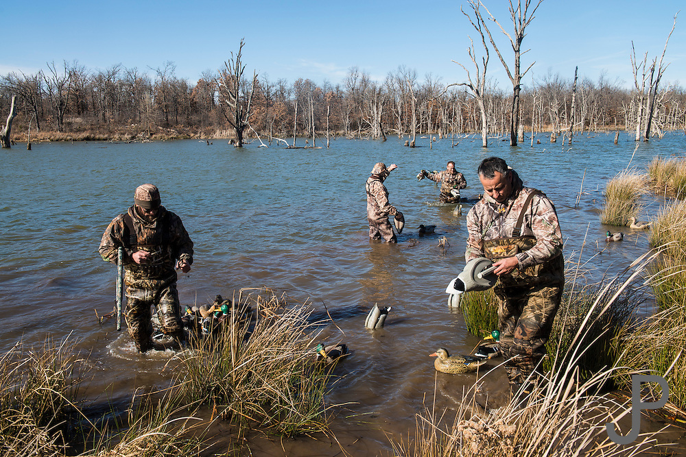 Duck hunters gather decoys after hunting on a private watershed lake in Shamrock, Oklahoma