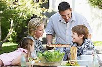 Family of four having lunch outdoors portrait