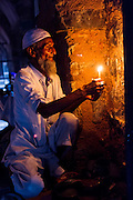 "27th August 2015, New Delhi, India.  A man who watches over peoples shoes while they pray holds a candle in the catacombs of Feroz Shah Kotla in New Delhi, India on the 27th August  2015<br /> <br /> PHOTOGRAPH BY AND COPYRIGHT OF SIMON DE TREY-WHITE a photographer in delhi<br /> + 91 98103 99809. Email: simon@simondetreywhite.com<br /> <br /> People have been coming to Firoz Shah Kotla to pray to and leave written notes and offerings for Djinns in the hopes of getting wishes granted since the late 1970's. Jinn, jann or djinn are supernatural creatures in Islamic mythology as well as pre-Islamic Arabian mythology. They are mentioned frequently in the Quran  and other Islamic texts and inhabit an unseen world called Djinnestan. In Islamic theology jinn are said to be creatures with free will, made from smokeless fire by Allah as humans were made of clay, among other things. According to the Quran, jinn have free will, and Iblīs abused this freedom in front of Allah by refusing to bow to Adam when Allah ordered angels and jinn to do so. For disobeying Allah, Iblīs was expelled from Paradise and called ""Shayṭān"" (Satan).They are usually invisible to humans, but humans do appear clearly to jinn, as they can possess them. Like humans, jinn will also be judged on the Day of Judgment and will be sent to Paradise or Hell according to their deeds. Feroz Shah Tughlaq (r. 1351–88), the Sultan of Delhi, established the fortified city of Ferozabad in 1354, as the new capital of the Delhi Sultanate, and included in it the site of the present Feroz Shah Kotla. Kotla literally means fortress or citadel."