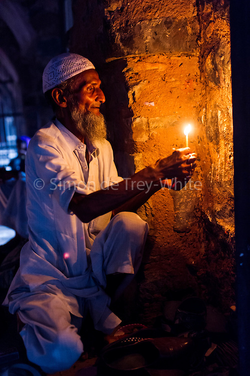 27th August 2015, New Delhi, India.  A man who watches over peoples shoes while they pray holds a candle in the catacombs of Feroz Shah Kotla in New Delhi, India on the 27th August  2015<br /> <br /> PHOTOGRAPH BY AND COPYRIGHT OF SIMON DE TREY-WHITE a photographer in delhi<br /> + 91 98103 99809. Email: simon@simondetreywhite.com<br /> <br /> People have been coming to Firoz Shah Kotla to pray to and leave written notes and offerings for Djinns in the hopes of getting wishes granted since the late 1970's. Jinn, jann or djinn are supernatural creatures in Islamic mythology as well as pre-Islamic Arabian mythology. They are mentioned frequently in the Quran  and other Islamic texts and inhabit an unseen world called Djinnestan. In Islamic theology jinn are said to be creatures with free will, made from smokeless fire by Allah as humans were made of clay, among other things. According to the Quran, jinn have free will, and Iblīs abused this freedom in front of Allah by refusing to bow to Adam when Allah ordered angels and jinn to do so. For disobeying Allah, Iblīs was expelled from Paradise and called &quot;Shayṭān&quot; (Satan).They are usually invisible to humans, but humans do appear clearly to jinn, as they can possess them. Like humans, jinn will also be judged on the Day of Judgment and will be sent to Paradise or Hell according to their deeds. Feroz Shah Tughlaq (r. 1351&ndash;88), the Sultan of Delhi, established the fortified city of Ferozabad in 1354, as the new capital of the Delhi Sultanate, and included in it the site of the present Feroz Shah Kotla. Kotla literally means fortress or citadel.