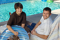 Father and son holding inflatable raft, sitting by side of swimming pool, portrait