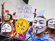 "02 JUNE 2013 - BANGKOK, THAILAND: Anti-government protesters wearing Guy Fawkes masks and carrying a fan with a picture of Bhumibol Adulyadej, the King of Thailand, march through Bangkok. The so called White Mask protesters are strong supporters of the Thai monarchy. About 300 people wearing the Guy Fawkes mask popularized by the movie ""V for Vendetta"" and Anonymous, the hackers' group, marched through central Bangkok Sunday demanding the resignation of Prime Minister Yingluck Shinawatra. They claim that Yingluck is acting as a puppet for her brother, former Prime Minister Thaksin Shinawatra, who was deposed by a military coup in 2006 and now lives in exile in Dubai.     PHOTO BY JACK KURTZ"