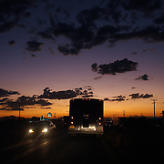 Traffic- cars trucks and busses- drive under a glowing sunset in Agua Perieta, Mexico.