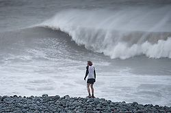 "© London News Pictures. 08/02/2014. Aberystwyth, UK. <br /> A runner watches gale force winds and big waves begin to strike the seafront at Aberystwyth on the west wales coast.  The winds are forecast to strengthen throughout the day, gusting up to 70 or 80 mph, and with the rising tide, their impact could be potentially damaging again. An amber ""be prepared"" warning  has been issued by the Met Office for wind,. Photo credit: Keith Morris/LNP"