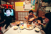 Saturday night meal at the Ukita house, always accompanied by the fifth member of the family: the television. Japan. Published in Material World: A Global Family Portrait, pages, 52-53. The Ukita family lives in a 1421 square foot wooden frame house in a suburb northwest of Tokyo called Kodaira City.