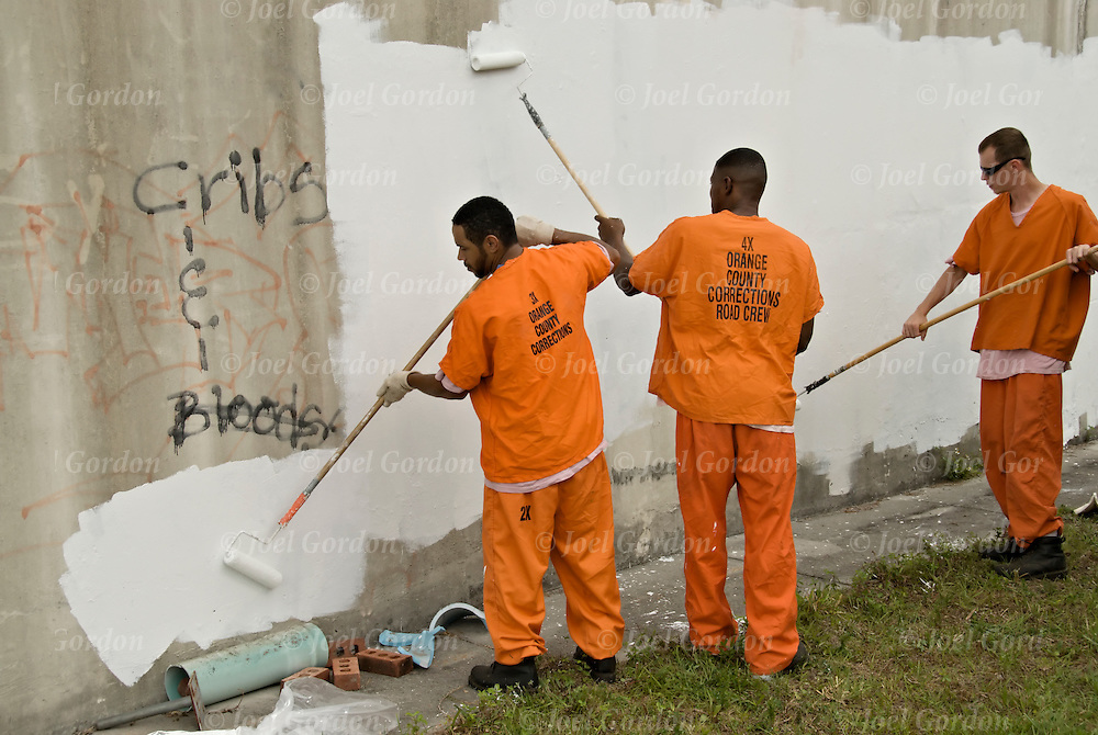 Graffiti eradication program of the Florida Orange County Correction Department. Work Inmates on road crew paint over gang graffiti on public land as  Correction Officer in background watch.  Correction Officer investigate gang activity in the Orange County area, map and track gang movement and identify Graffiti.  Bloods is the main group, each group has a set. IBO is an Orlando set for the west coast Blood Gang.   IBO - I Bomb Orlando - Blood set that operates in South Orlando..releases # 2432, 2433, 2435, 2436