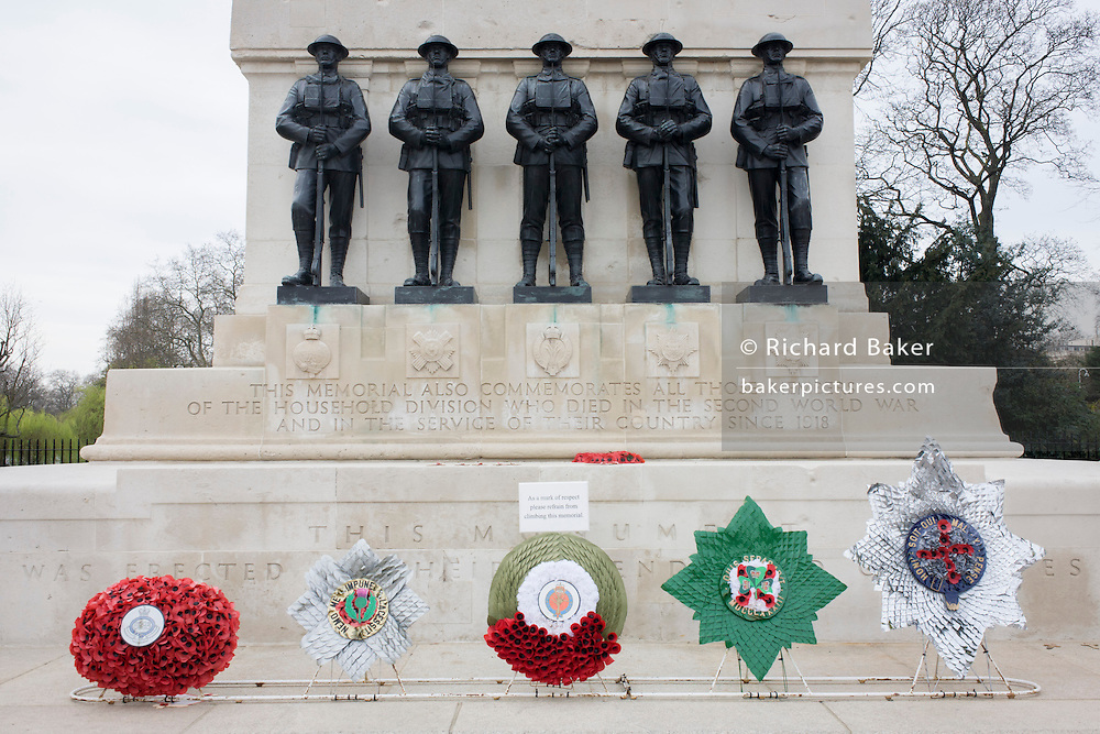 Wreaths with Five soldiers standing at ease on the memorial to both first and second world wars in Westminster.
