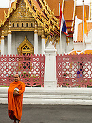 "21 JULY 2013 - BANGKOK, THAILAND:   A Buddhist monk at Wat Benchamabophit waits for people to present them with alms on the first day of Vassa, the three-month annual retreat observed by Theravada monks and nuns. On the first day of Vassa (or Buddhist Lent) many Buddhists visit their temples to ""make merit."" During Vassa, monks and nuns remain inside monasteries and temple grounds, devoting their time to intensive meditation and study. Laypeople support the monastic sangha by bringing food, candles and other offerings to temples. Laypeople also often observe Vassa by giving up something, such as smoking or eating meat. For this reason, westerners sometimes call Vassa the ""Buddhist Lent.""      PHOTO BY JACK KURTZ"
