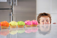 Young boy peeking over counter at row of cupcakes in kitchen