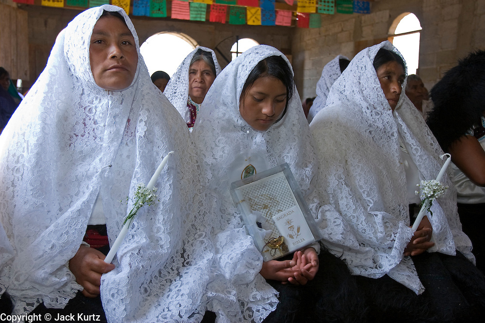 """25 APRIL 2005 - SAN CRISTOBAL DE LAS CASAS, CHIAPAS, MEXICO: First communion mass in the Chamulan Indian community of Yaaltsunum near San Cristobal de las Casas. The Catholic Church in the Chiapas highlands is facing a threat from evangelical Protestant churches, which are experiencing explosive growth, and from """"traditionalist"""" Catholic churches, which are not affiliated with the San Cristobal diocese and are controlled by local politicians and powerful indigenous leaders affiliated with the politicians. The traditionalists burn down churches and chapels affiliated with the diocese, threaten the priests and put indigenous men who worship with the diocese in jail.  PHOTO BY JACK KURTZ"""