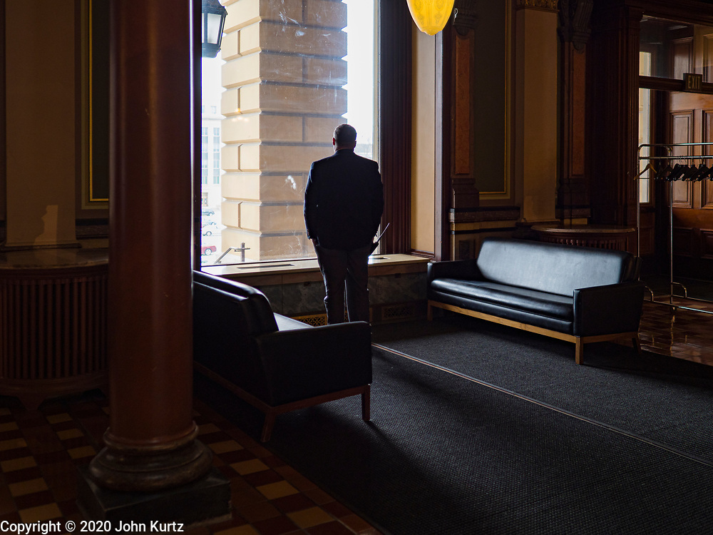 """16 MARCH 2020 - DES MOINES, IOWA: A security guard looks out a window at the State Capitol in Des Moines. Because of numerous reports of Coronavirus in Iowa, the governor is suspending the legislative session for 30 days. It was scheduled to run until mid-April. Sunday night, the Governor announced that the state health department had recorded """"community spread"""" in Des Moines. As a result the State Capitol instituted mitigation measures that included mandatory health screening for everyone going into the building, canceling group tours of the building, and closing the souvenir shop and snack bar.     PHOTO BY JACK KURTZ"""