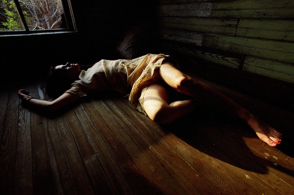A young woman with bare legs lying on a wooden floor