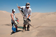 Sandboarding instructors, Gerson Valle, front, and Elia Pons, work to build a jump in the dunes surrounding Huacachina in Peru.