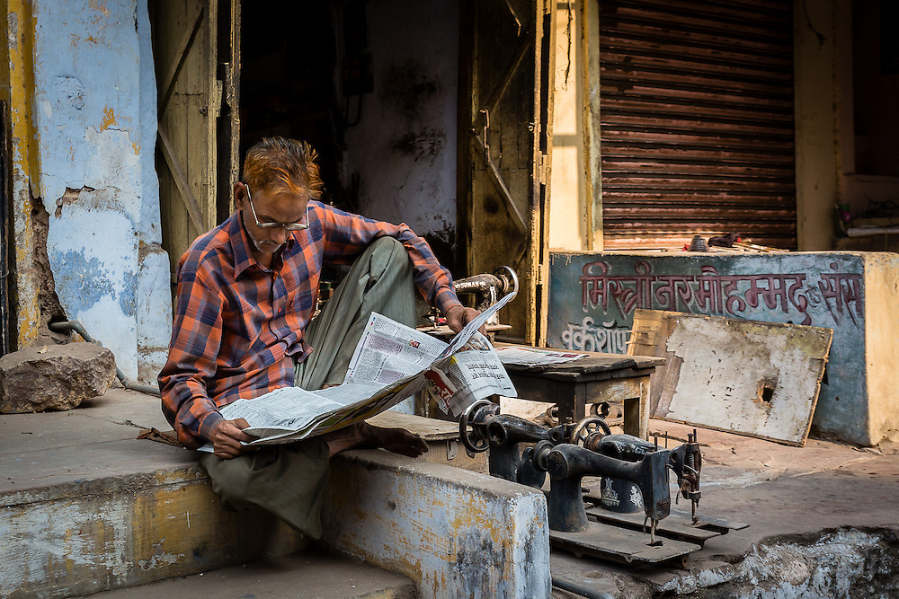 A man sits by the front of his shop, in the main street of Bundi, reading the early morning news.