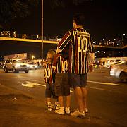 An adult and two youngsters, all wearing identical shirts, wait for a taxi after the Fluminense FC V CR Vasco da Gama Futebol Brasileirao League match at the Maracana, Jornalista Mário Filho Stadium, Rio de Janeiro,  Brazil. 22nd August 2010. Photo Tim Clayton.