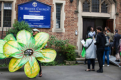 London, UK. 14th June, 2018. Large green Grenfell flowers are arranged outside the Grenfell Memorial Service at St Helen's Church.