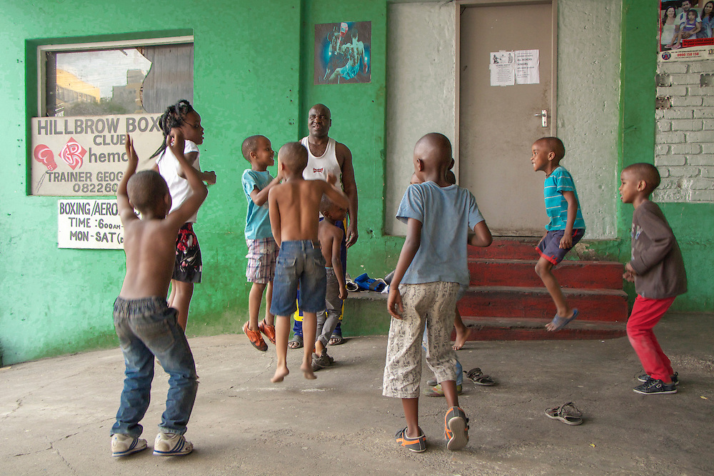 George Khusi, a former professional boxer and founder of the Hillbrow Boxing Club, leads a group of children through warm-up dyring a trainign session. The club offers an after school programme for the neighbourhood kids that provides disciples and keeps them away from the streets. Some children who started out this way became national champions.