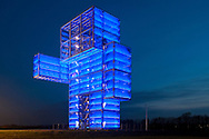 Europe, Germany, North Rhine-Westphalia, the illuminated Indemann near the village Lucherberg in the district Dueren east of the city of Aachen on top of the man-made spoil heap Goltsteinkuppe, the Indemann is a 36 meter high look-out made of 280 tons of steel with 20.000 parts. With his right arm he points to the brown coal open-cast mining Inden.<br />