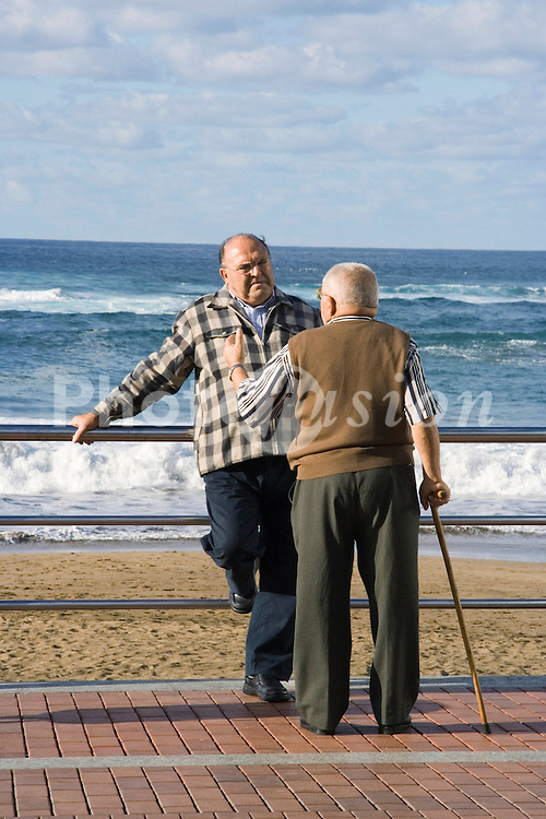 Two old men talking on the sea front in the Canary Islands,
