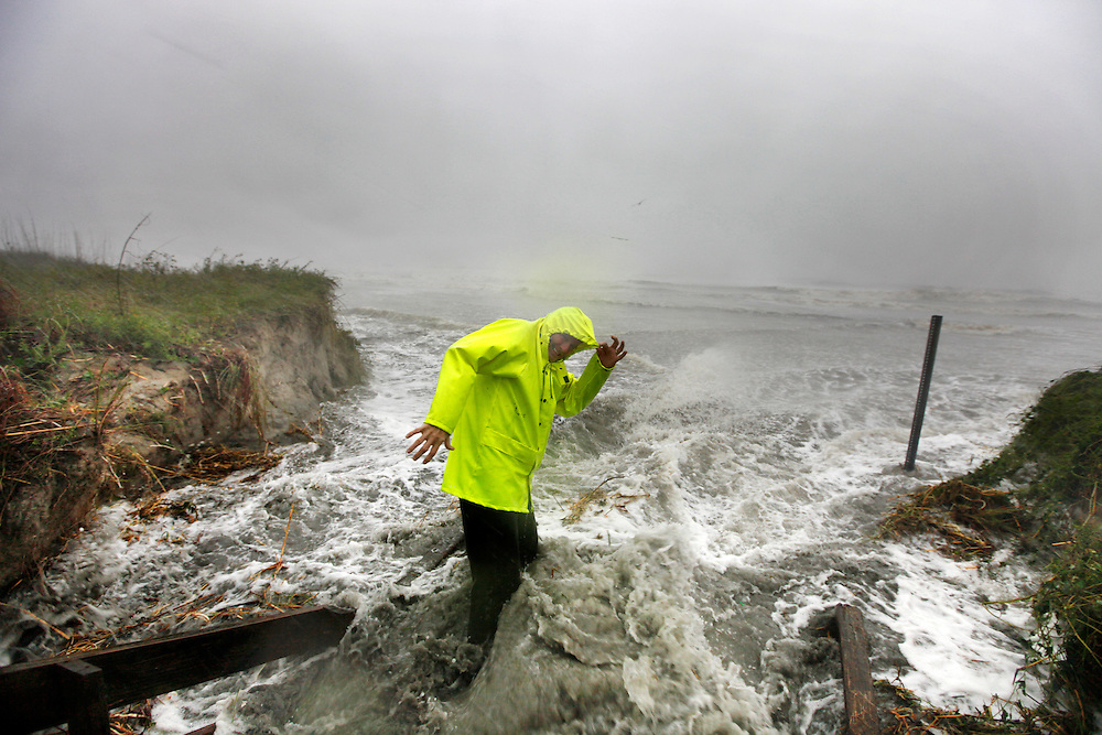 David Reedy of North Carolina wades in surging ocean water from Hurricane Matthew during low tide Saturday morning in Isle of Palms. The waves bowled over boardwalks at high tide and continued eroding sand dunes as the tide subsided. (ANDREW KNAPP/STAFF)