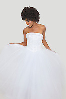 Beautiful African American bride in white wedding dress standing against plain background