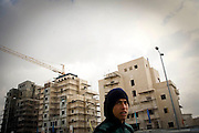 A Palestinian worker walks past unfinished buildings in Har Homa. Image © Angelos Giotopoulos/Falcon Photo Agency