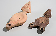 Two Roman era terracotta oil lamps 1st century CE one nozzle on the left and two nozzle sample on the right