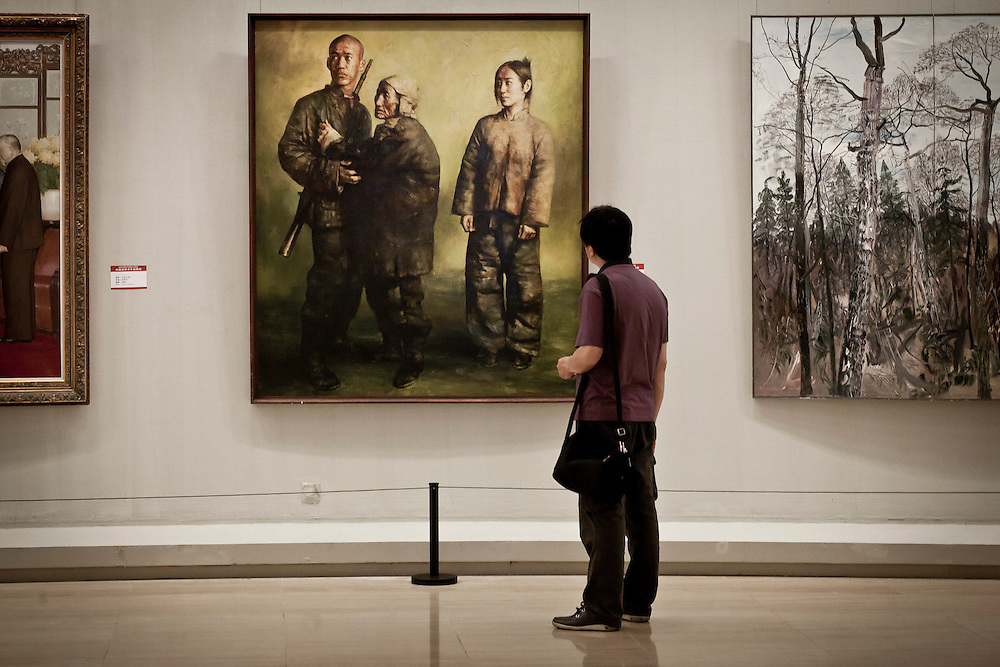 A young chinese is looking at paintings in an official exhibition organized for the celebration of the 90 years of the Communist Party. Classic paintings emphasize traditionnal propaganda topics like the unity of the country in the war of resistance against Guomingdang and Japan...
