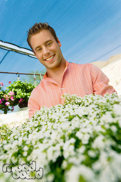 Smiling Young Man in Greenhouse