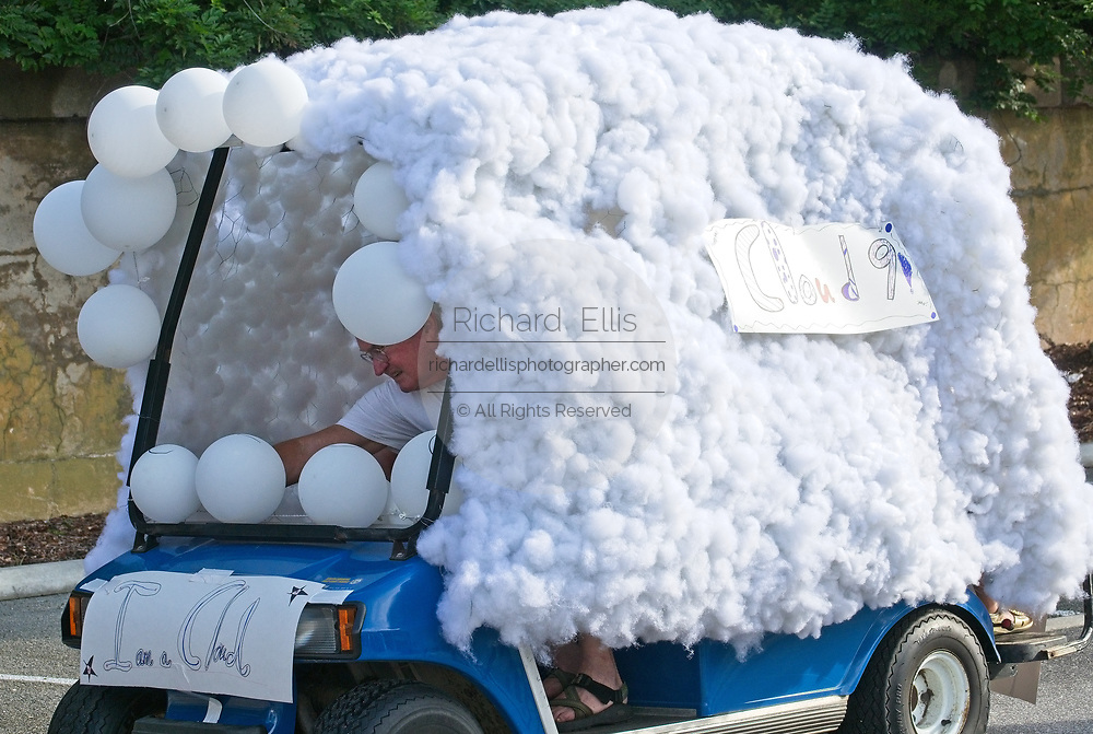 "A man arranges balloons on his ""Cloud 9"" decorated golf cart during the annual Sullivan's Island Independence Day parade July 4, 2017 in Sullivan's Island, South Carolina. The tiny affluent sea island hosts a bicycle and golf cart parade through the historic village."