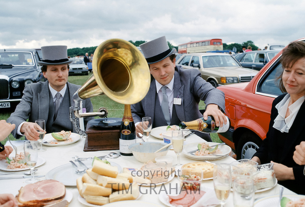 Racegoers in traditional top hat and tails have champagne picnic with old-fashioned gramophone at Epsom Racecourse on Derby Day, UK