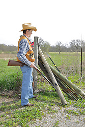 An aging man is dressed to hunt in denim and a hunting vest with elastic loops to hold shell, and a game pocket on the back. Completing the ensemble is a straw cowboy hat, cowboy boots and a 12 gauge side by side double barrel shotgun. Wood and Steel fence posts are stacked together with the spares leaning against strands of barbed wire that complete the fence. This image available for EDITORIAL USE ONLY. A release may be required. Additional information by contacting alook at alanlook.com