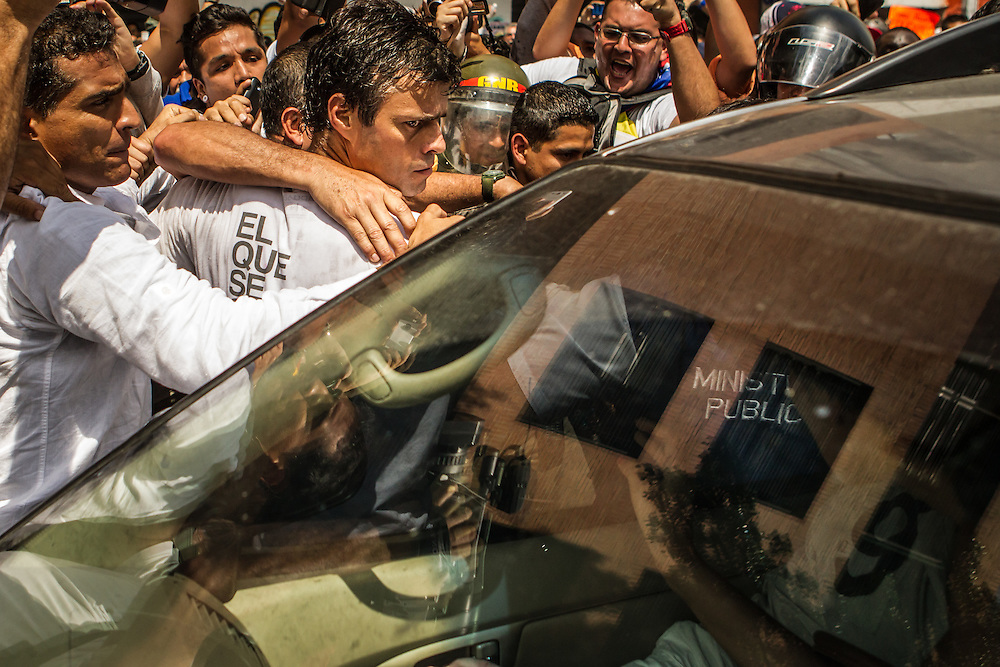 CARACAS, VENEZUELA - FEBRUARY 18, 2014: Opposition leader Leopoldo López is transferred from an armored vehicle to a   a black SUV by the police. Thousands of people took to the streets today to support López as he surrendered to Police during a peaceful march in Caracas.  The government has said López is responsible for inciting recent street protests, that have killed three people. CREDIT: Meridith Kohut for The New York Times