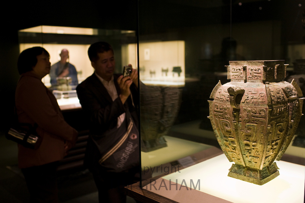 Visitors look at a water vessel on display in glass case at the Shanghai Museum, China