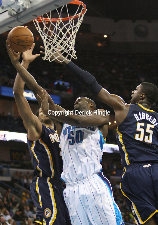 Feb 19, 2010; New Orleans, LA, USA; New Orleans Hornets center Emeka Okafor (50) shoots past Indiana Pacers forward Danny Granger (33) and center Roy Hibbert (55) during the second half at the New Orleans Arena. The Hornets defeated the Pacers 107-101.  Mandatory Credit: Derick E. Hingle-US PRESSWIRE