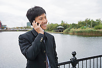 Happy mid adult businessman using cell phone at bridge railing