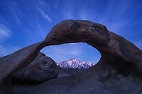 Twilight sky and wispy clouds over the Sierra Nevada Mtns and Mobius Arch in Alabama Hills Recreation Area, CA, USA
