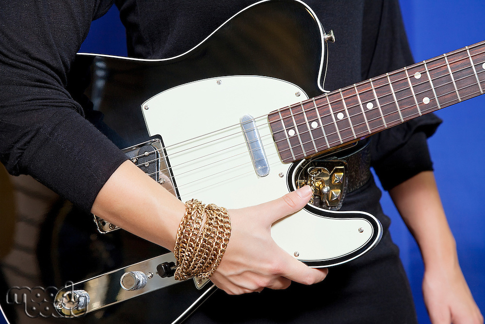 Midsection of young woman holding electric guitar