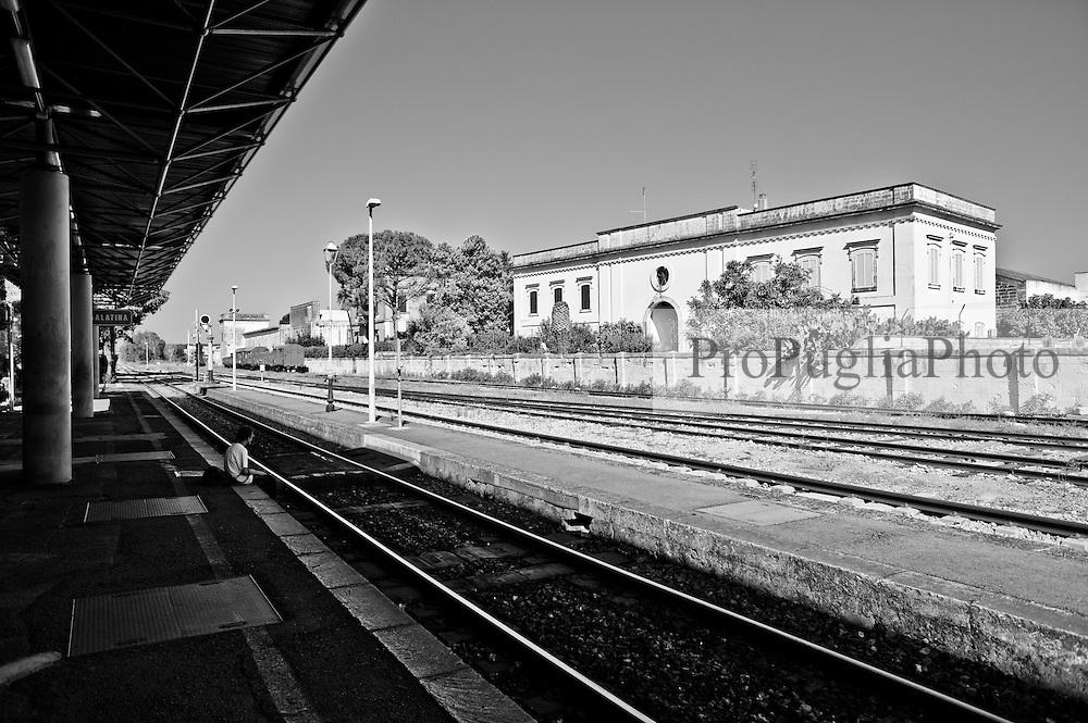 un passeggero attende l'arrivo del treno seduto sulla banchina a ridosso del binario. Reportage che analizza le situazioni che si incontrano durante un viaggio lungo le linee ferroviarie delle Ferrovie Sud Est nel Salento