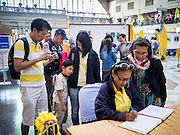"05 DECEMBER 2013 - BANGKOK, THAILAND:  People sign a book sending birthday greetings to Bhumibol Adulyadej, the King of Thailand, at Hua Lamphong Train Station in Bangkok on the  King's 86th birthday. Dec. 5, the King's Birthday, is a national holiday in Thailand, and is also celebrated as the country's ""Fathers' Day."" The State Railways of Thailand put on special trains to take people to the King's ""Summer Palace"" in the oceanside community of Hua Hin where the King granted a public audience. There were also merit making ceremonies throughout the country.  Many people wear yellow on the King's Birthday because yellow is the color associated with his reign. As of 2013, he was the longest reigning monarch in the world.          PHOTO BY JACK KURTZ"