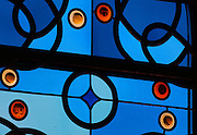 Detail of the stained glass window, with blue glass and leadwork in circles and the interlacing patterns reminiscent of the Neo-Romanesque style of the 19th century, made by Ateliers Loire, Chartres, in the Bell tower room themed 'Le Merveilleux' or The Supernatural, first floor, in Le Tresor de la Cathedral d'Angouleme, in Angouleme Cathedral, or the Cathedrale Saint-Pierre d'Angouleme, Angouleme, Charente, France. The 12th century Romanesque cathedral was largely reworked by Paul Abadie in 1852-75. In 2008, Jean-Michel Othoniel was commissioned by DRAC Aquitaine - Limousin - Poitou-Charentes to display the Treasure of the Cathedral in some of its rooms, which opened to the public on 30th September 2016. Picture by Manuel Cohen. L'autorisation de reproduire cette oeuvre doit etre demandee aupres de l'ADAGP/Permission to reproduce this work of art must be obtained from DACS.