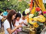 "12 JULY 2014 - PHRA PHUTTHABAT, SARABURI, THAILAND: A woman and her daughter pray before the Tak Bat Dok Mai at Wat Phra Phutthabat in Saraburi province of Thailand. Wat Phra Phutthabat is famous for the way it marks the beginning of Vassa, the three-month annual retreat observed by Theravada monks and nuns. The temple is highly revered in Thailand because it houses a footstep of the Buddha. On the first day of Vassa (or Buddhist Lent) people come to the temple to ""make merit"" and present the monks there with dancing lady ginger flowers, which only bloom in the weeks leading up Vassa. They also present monks with candles and wash their feet. During Vassa, monks and nuns remain inside monasteries and temple grounds, devoting their time to intensive meditation and study. Laypeople support the monks by bringing food, candles and other offerings to temples. Laypeople also often observe Vassa by giving up something, such as smoking or eating meat. For this reason, westerners sometimes call Vassa ""Buddhist Lent.""    PHOTO BY JACK KURTZ"