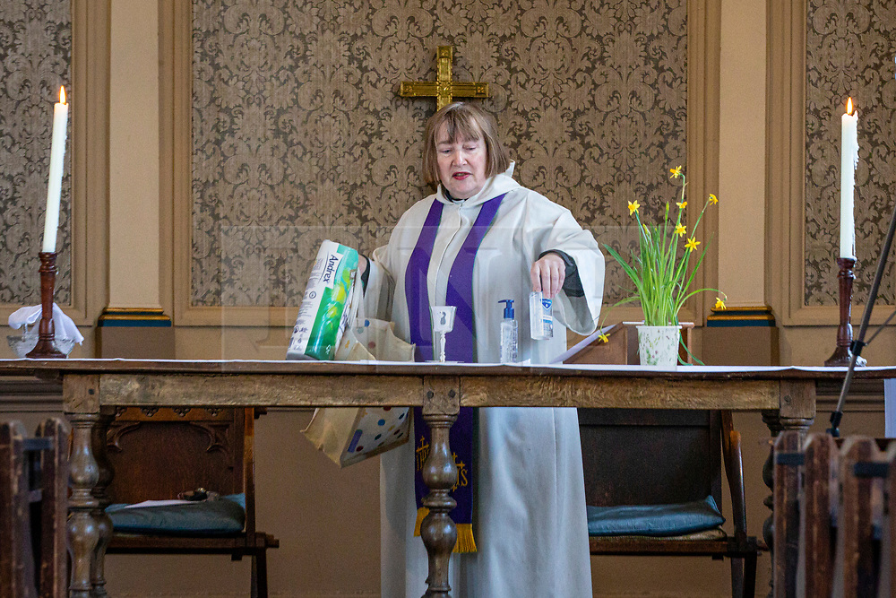 © Licensed to London News Pictures. 22/03/2020. London, UK. Reverend Anne Bennett holds up a packet of toilet paper and hand sanitiser as she delivers the sermon during the Mothering Sunday service to parishioners via live-stream at the Church of the Ascension in Blackheath, south London. The items were donated by worshippers for the vulnerable members of the community. In response to government advice on social distancing and non-essential contact, the Church of England has suspended public worship until further notice to help slow the spread of the Coronavirus. Photo credit: Rob Pinney/LNP