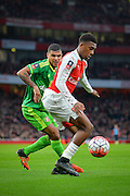 Arsenal Forward Alex Iwobi holds off Sunderland Defender DeAndre Yedlin during the The FA Cup match between Arsenal and Sunderland at the Emirates Stadium, London, England on 9 January 2016. Photo by Adam Rivers.