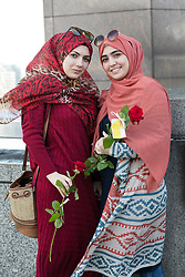 "© Licensed to London News Pictures. 11/06/2017. LONDON, UK.  Two muslim women friends pose for a photograph on London Bridge with a red rose. 1,000 red roses with messages of ""love and solidarity"" were given to passers by on London Bridge today.  Photo credit: Vickie Flores/LNP"