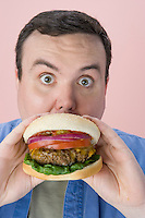 Overweight mid-adult man eating hamburger