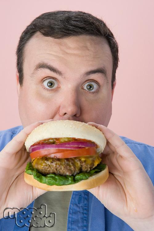 Overweight mid-adult man eating hamburger